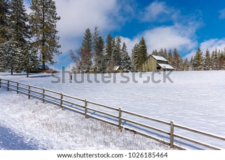 A rural scenic view of a fence by a snow covered field