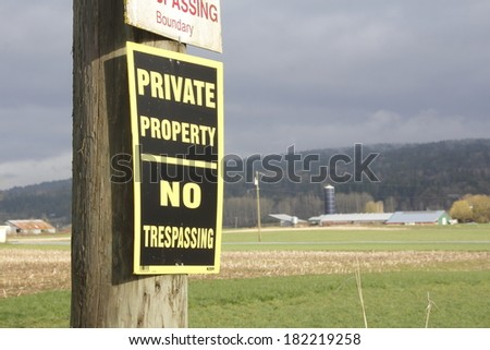 A rural sign on a farm warns that this is private property and no trespassing/Private Property No Trespassing/A rural sign on a farm warns that this is private property and no trespassing