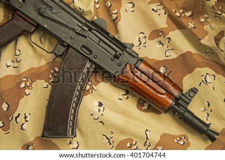 A Russian AKS-74U assault rifle, lying on US designed six-colour desert pattern camouflage, commonly known as chocolate chip. - stock photo