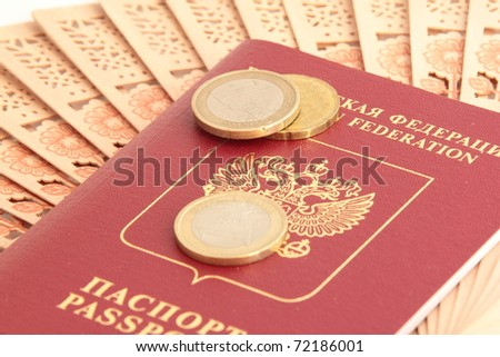 A Russian foreign passport with euro coins and a fan - stock photo