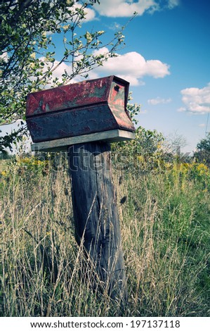 A rusted, old mailbox in an overgrown field. - stock photo