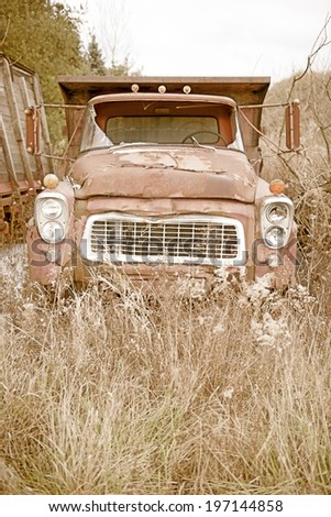 A rusted old truck with a broken windshield. - stock photo