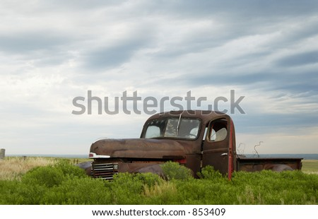 A rusted-out truck abandoned in a pasture. - stock photo
