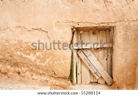 A rustic door, made of wood boards, on a wall made of adobe (clay and straws). The photo was taken at one of the many small villages of the province of Soria, Spain (Europe). - stock photo