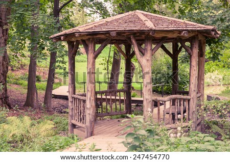 A rustic looking gazebo in a peaceful setting. - stock photo