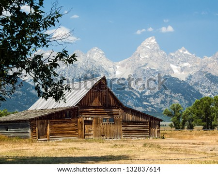 A rustic old barn on Mormon Row in the Antelope Flats area of Grand  Teton National Park, Wyoming with the peaks of the Cathedral Group against a blue sky - stock photo