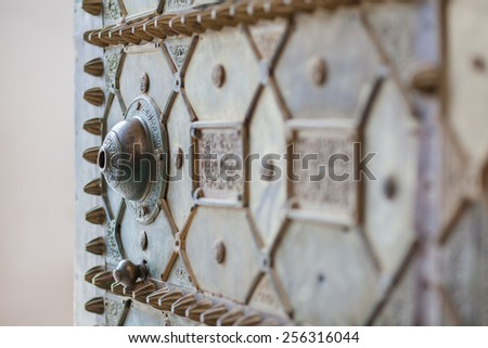 A rustic old metal door with broken door handle - stock photo