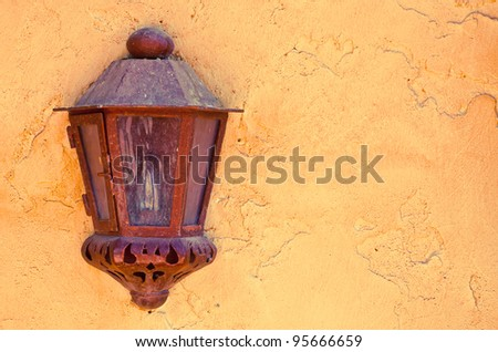 A rustic old metal lantern mounted on a wall - stock photo