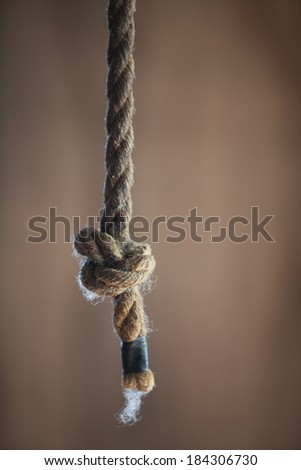 A rustic, old rope hanging down with a simple not tied in the end.  Shallow depth of field. - stock photo