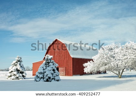 A rustic red barn in Ohio covered in fresh snow with a bright blue sky background.