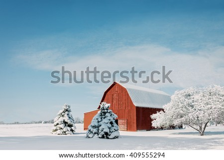 A rustic red Ohio barn covered in fresh snow with a bright blue sky background. - stock photo