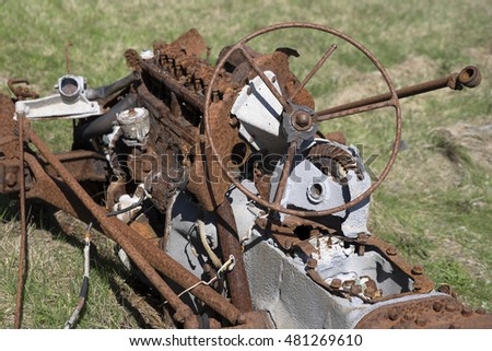 A rusty car wreck in its final resting place in a field