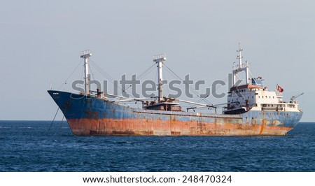 A Rusty Cargo Ship is anchored in Sea