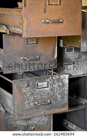 A rusty filing cabinet with empty drawers, pulled open. - stock photo