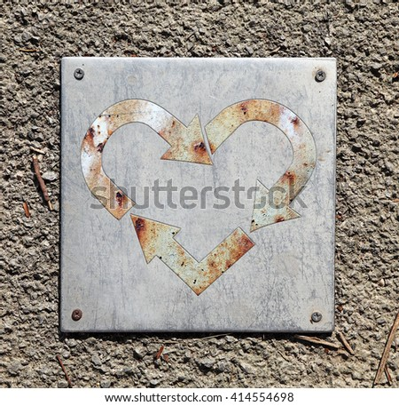 A rusty heart shaped recycle symbol on a metal plate on a rugged concrete surface.