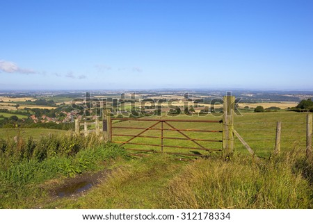a rusty metal gate overlooking the patchwork fields of the vale of york under a blue sky in summer - stock photo