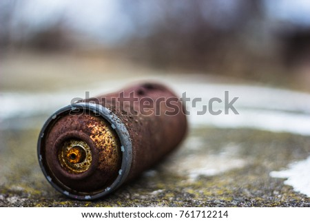 A rusty, old spray can lays on a concrete surface. The oxidized metal turned brownish over the years.