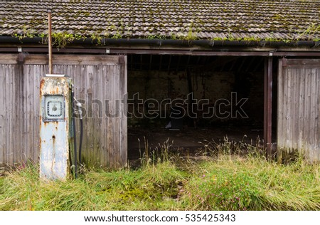 A rusty old vintage petrol pump abandoned in a rustic setting, next to a barn.