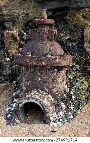 A rusty valve and pipe with barnacles on it. - stock photo