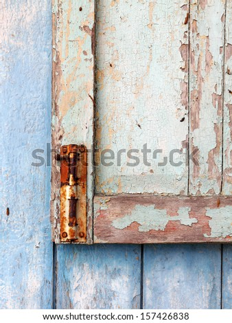 A rusty vintage window latch on a old grungy timber window panel.  - stock photo