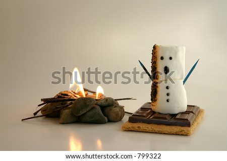 A s'more snowman gets a bit too close to the fire and is on his way to becoming a tasty treat. - stock photo