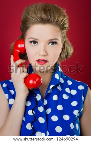 a 50s style housewife gossiping in a red vintage phone - stock photo