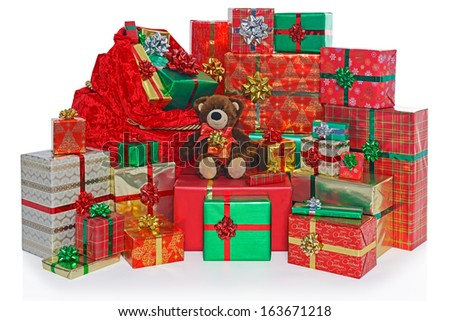 A sack and group of gift wrapped Christmas presents with a homemade teddy bear, isolated on a white background.
