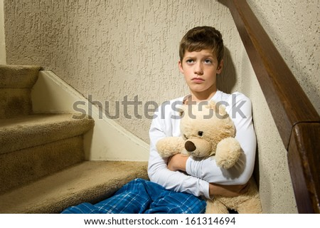 A sad and angry boy is sitting in the corner of a staircase - stock photo