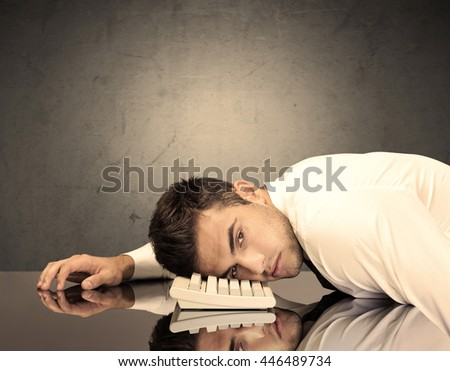 A sad and depressed office worker resting his head on a keyboard while shouting in front of a grey grungy wall background - stock photo