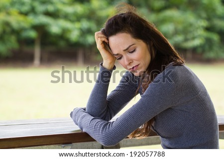 A sad and upset woman sitting down alone outdoors - stock photo