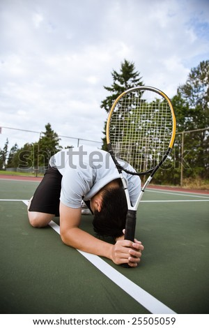 A sad asian tennis player kneeling down in disappointment after defeat - stock photo