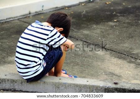 sad boy sitting on street alone 写真素材 704833609 shutterstock