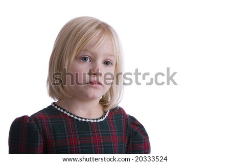 A sad child in a plaid dress on a white background