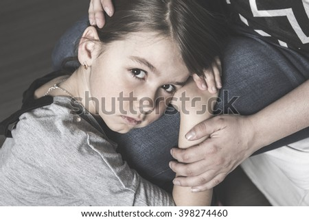 A sad daughter hugging his mother on the living room