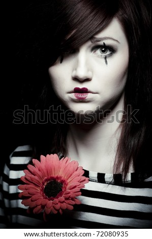 a sad female mime clown with a red flower - stock photo