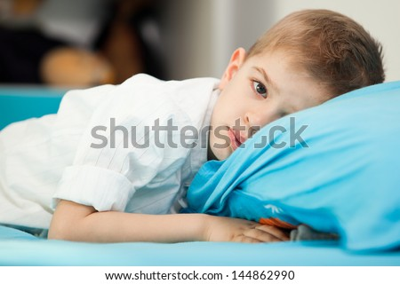 A sad five year old child sitting in his bed with his head on a blue pillow - stock photo