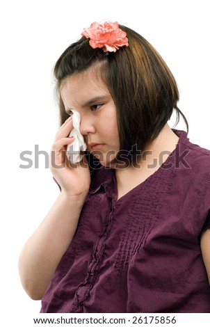 A sad girl is wiping her eyes with a tissue, isolated against a white background - stock photo