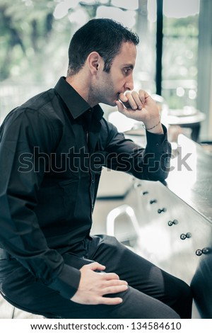 a sad, handsome man sitting at a bar with a pensive attitude - stock photo
