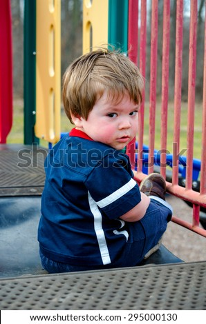 a sad little boy sits alone at a colorful outdoor playground