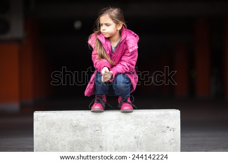 A sad little girl crouching down in pink - stock photo