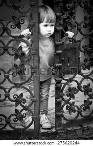 A sad little girl standing near metal gates - stock photo