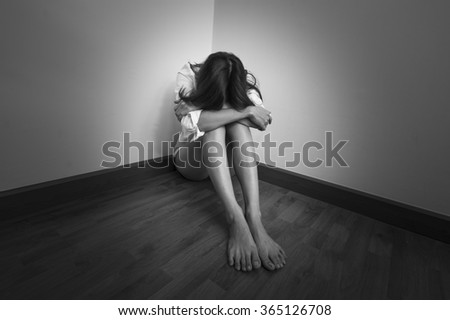 A sad woman sitting alone in a empty room at the corner - stock photo