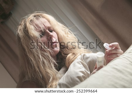 A sad woman taking medication on bed. - stock photo