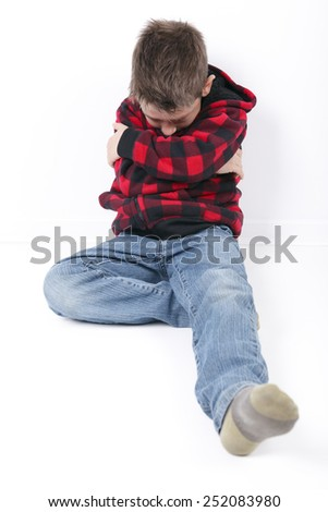 A sad young boy sit on white background - stock photo