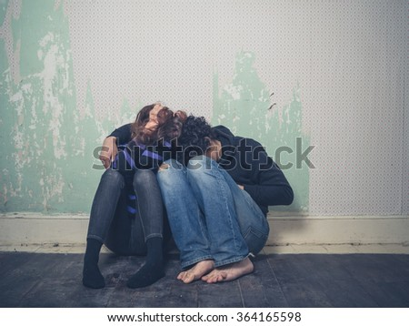 A sad young couple is sitting huddled up on  the floor in an empty room