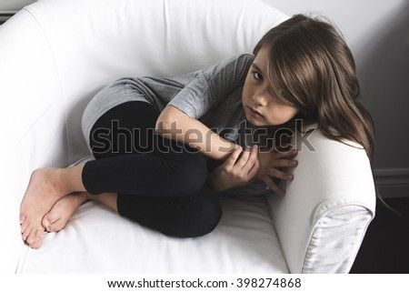 A sad young girl lay on sofa - stock photo