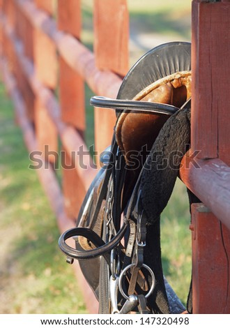 A saddle and bridle  lying  on a fence, after riding - stock photo