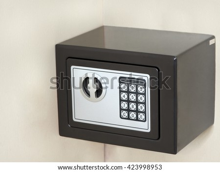 A safe with an electronic keypad is mounted against the wall.