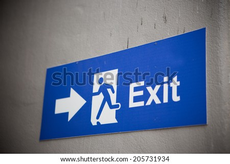 A safety exit sign with dark vignetting. - stock photo