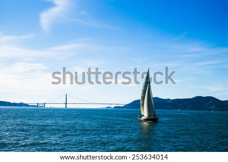 A Sail Boat in Front of the Golden Gate Bridge - stock photo